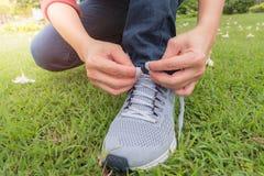 Спортсмен сидит вниз к веревочке ботинка в саде и стоковое фото