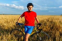 Спортсмен сидя на велосипеде Нося шестерня, шлем и стекла спорт Естественная предпосылка Красивое, голубое небо стоковые фото