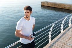 Спортсмен стоя около моря и питьевой воды Стоковые Фото