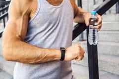 Спортсмен с бутылкой воды отдыхающ и проверяющ его умный вахта после бежать фитнес, спорт, стоковая фотография