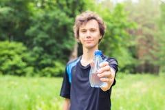 Спортсмен с бутылкой воды после бежать outdoors в парке Стоковая Фотография RF