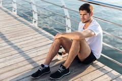 Спортсмен с бутылкой усаживания и ослаблять воды на пристани Стоковое Фото