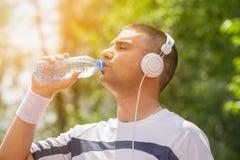 Спортсмен с питьевой водой наушников от пластичной бутылки Стоковая Фотография RF