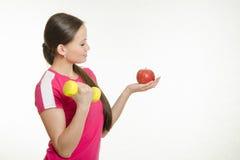 Спортсмен трясет мышцы правой гантели и смотреть яблоко в ее левой руке Стоковая Фотография RF