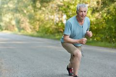 Спортсмен убежденный собственной личностью старший готовый для того чтобы начать jogging марафон, слушает музыка, который нужно р стоковые изображения