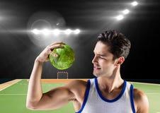 Спортсмен flxing его рука пока держащ гандбол против стадиона в предпосылке Стоковые Фотографии RF