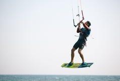 Спортсмен Kiteboarder выполняя kiteboarding kitesurfing фокусы Стоковая Фотография