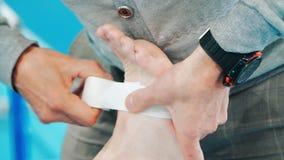 Спорт врачуют давать скорую помощь спортсмену во время ушиба Руки кладя гипсолит видеоматериал
