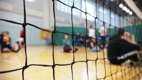 Спорт для людей с ограниченными возможностями Люди сидя на поле и играя волейбол Решетка в фокусе акции видеоматериалы