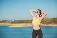 Спорт ее жизнь Здоровые концепции образа жизни и спорта Привлекательная молодая женщина в спорт одежде и стоять и str наушников стоковые изображения