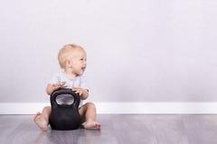 Спорт жизнь Счастливый смеясь над малыш сидя на поле с kettlebell скопируйте космос Стоковое Фото
