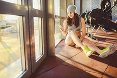 Спорт, здоровье и технология темы красивая сексуальная кавказская спортсменка женщины в серых sportswear и шляпе сидит окном с со стоковое фото