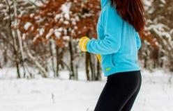 Спорт зимы в лесе в свежем воздухе Женщина в tracksuit бежит в парке в зиме стоковое изображение
