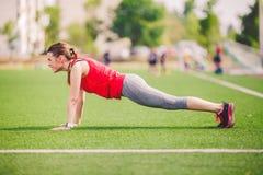 Спорт и здоровье темы Молодая кавказская женщина делая подогрев, нагревающ мышцы, тренируя подбрюшные мышцы Теряя живот стоковые изображения rf