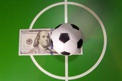 Спорт и концепция денег - забавляйтесь футбольный мяч в центре поля, в центре зеленого поля и банкноте в 100 долларах дальше Стоковое Фото