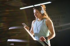 Спорт и музыка темы Красивая кавказская женщина бежать в спортзале на третбане На головных больших белых наушниках, девушка слуша Стоковое Изображение RF