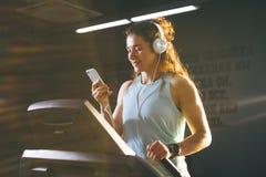 Спорт и музыка темы Красивая кавказская женщина бежать в спортзале на третбане На головных больших белых наушниках, девушка слуша Стоковые Фотографии RF