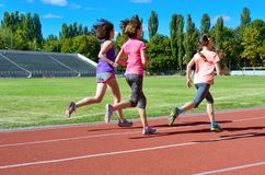 Спорт и фитнес семьи, счастливая мать и дети бежать на стадионе отслеживают outdoors, концепция образа жизни детей здоровая стоковые изображения rf