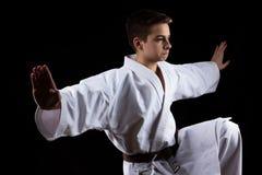 Спорт карате военный с молодым мальчиком в кимоно, черной предпосылке, стоковые изображения