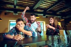 Спорт, люди, отдых, приятельство и концепция развлечений - счастливые футбольные болельщики или мужские друзья выпивая пиво и стоковое фото