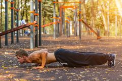 Спорт Молодой атлетический делать человека нажим-поднимает Мышечный и сильный работать парня стоковое фото rf