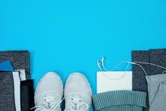 Спорт образа жизни фитнеса здоровый активный обувает шляпу цветков предпосылки одежд наушников тапок взгляд сверху голубую белую стоковые изображения rf