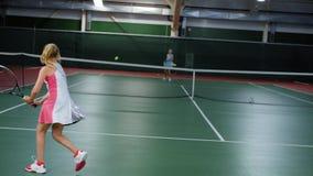 Спорт тренируя на теннисе для подростков, детей бросают шарик через сеть с помощью ракеткам, активным сток-видео