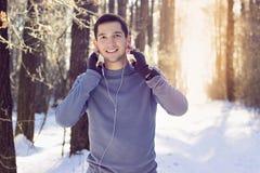 Спорт укомплектовывают личным составом слушая музыку в лесе и усмехаться Зима Стоковая Фотография RF