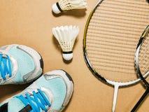 Спорт установили голубых ботинок и shuttlecocks спорта с ракеткой бадминтона 2 на предпосылке переклейки Стоковая Фотография