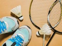 Спорт установили голубых ботинок и shuttlecocks спорта с ракеткой бадминтона 2 на предпосылке переклейки Стоковое Изображение