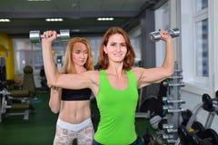 Спорт, фитнес, концепция образа жизни - женщина делая комод и гантель плеча отжимают при личный тренер помогая ей Стоковые Изображения