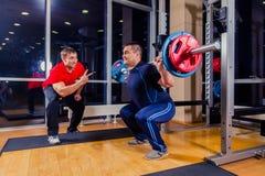 Спорт, фитнес, сыгранность, занимаясь культуризмом концепция людей - человек и личный тренер при штанга изгибая мышцы в спортзале Стоковая Фотография RF