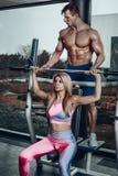 Спорт, фитнес, сыгранность, культуризм и концепция людей - молодая женщина и личный тренер с изгибать штанги Стоковая Фотография