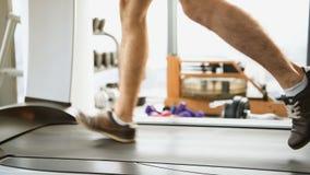 Спорт, фитнес, технология и концепция людей - близкая вверх мужских ног бежать на третбане в спортзале видеоматериал