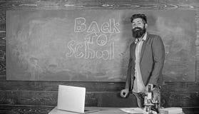 Способность работы учителя запальчиво достигает вне студентов Учитель около доски держит мел пишет надпись назад к школе стоковое изображение rf