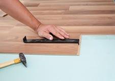 справляться устанавливающ ламинат Человек устанавливая новый прокатанный деревянный настил Работник устанавливая деревянный слоис стоковое фото rf