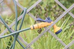 Спринклер и шланг вися дальше обнесли забором сад Стоковое Изображение