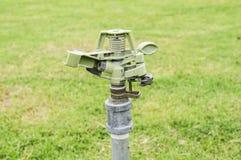 Спринклер на зеленой лужайке Стоковое Изображение