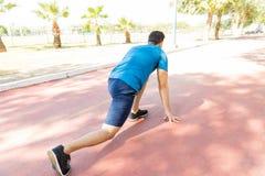 Спринтер в Sportswear заискивая на исходном рубеже в парке стоковое фото rf