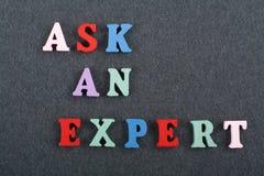 СПРОСИТЕ ЭКСПЕРТНОЕ слово на черной предпосылке доски составленной от писем красочного блока алфавита abc деревянных, скопируйте  стоковые фото