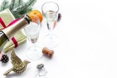 Спрус, мандарин, шампанское, настоящий момент и игрушки для торжества рождества на белом модель-макете предпосылки Стоковые Изображения