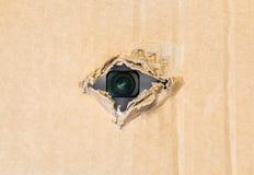 Спрятанная камера в сорванном отверстии в бумаге картона стоковая фотография rf