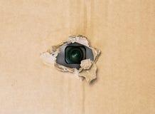 Спрятанная камера в сорванном отверстии в бумаге картона стоковые фотографии rf