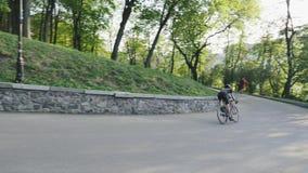 Спускать всадника велосипеда быстрый вниз с холма в парке Шлем велосипедиста нося на curvy покатой дороге ( акции видеоматериалы