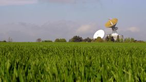 Спутниковая антенна-тарелка в сельской местности Телескоп космоса отслеживая на широком зеленом поле сток-видео