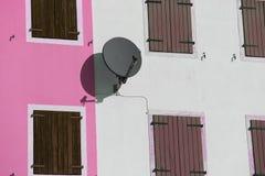 Спутниковая антенна-тарелка для того чтобы получить программы спутникового телевидения на стене стоковое фото rf
