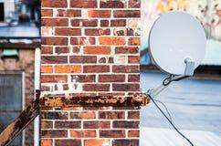 Спутниковая антенна-тарелка на печной трубе кирпича стоковая фотография rf