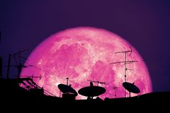 спутниковые антенна-тарелки полного клубники луны планеты силуэта назад на крыше стоковые изображения rf