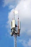 спутниковые антенна-тарелки и плиты на шпиле башни для радиосвязей и интернете против неба Стоковая Фотография