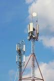 спутниковые антенна-тарелки и плиты на шпиле башни для радиосвязей и интернете против неба Стоковое Изображение RF